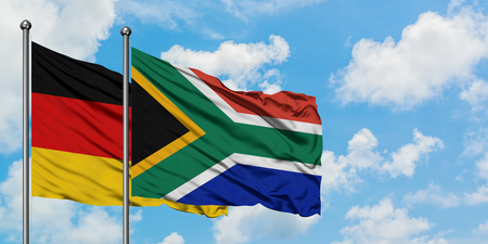 Germany and South Africa flag waving in the wind against white cloudy blue sky together. Diplomacy concept, international relations.