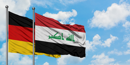 Germany and Iraq flag waving in the wind against white cloudy blue sky together. Diplomacy concept, international relations.
