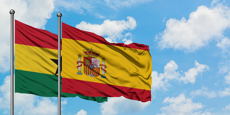 Ghana and Spain flag waving in the wind against white cloudy blue sky together. Diplomacy concept, international relations. Stock Photo