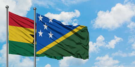 Ghana and Solomon Islands flag waving in the wind against white cloudy blue sky together. Diplomacy concept, international relations.