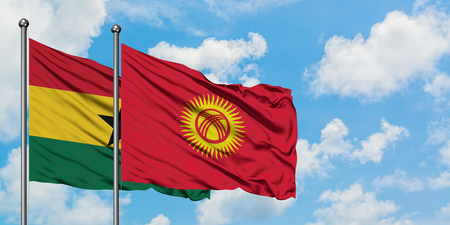 Ghana and Kyrgyzstan flag waving in the wind against white cloudy blue sky together. Diplomacy concept, international relations.