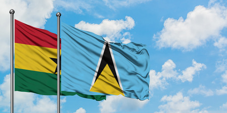 Ghana and Saint Lucia flag waving in the wind against white cloudy blue sky together. Diplomacy concept, international relations.
