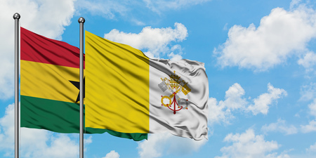 Ghana and Vatican City flag waving in the wind against white cloudy blue sky together. Diplomacy concept, international relations.