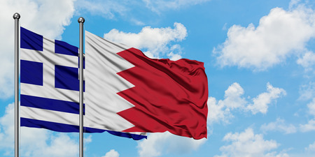 Greece and Bahrain flag waving in the wind against white cloudy blue sky together. Diplomacy concept, international relations. Standard-Bild