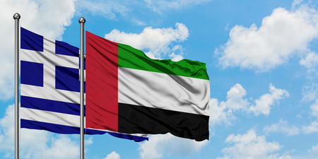 Greece and United Arab Emirates flag waving in the wind against white cloudy blue sky together. Diplomacy concept, international relations. Stock Photo