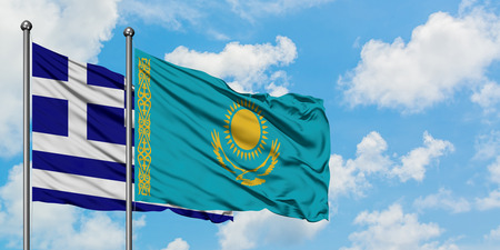 Greece and Kazakhstan flag waving in the wind against white cloudy blue sky together. Diplomacy concept, international relations.