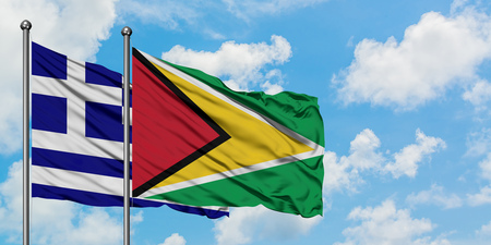 Greece and Guyana flag waving in the wind against white cloudy blue sky together. Diplomacy concept, international relations. Standard-Bild