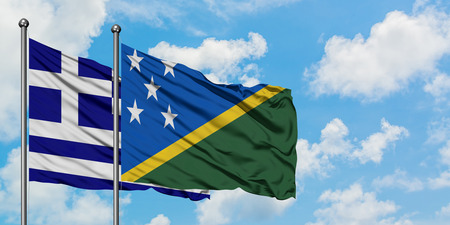 Greece and Solomon Islands flag waving in the wind against white cloudy blue sky together. Diplomacy concept, international relations.