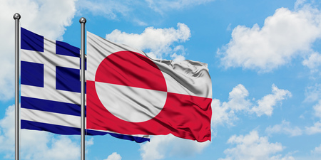 Greece and Greenland flag waving in the wind against white cloudy blue sky together. Diplomacy concept, international relations. Stock Photo