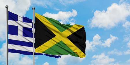 Greece and Jamaica flag waving in the wind against white cloudy blue sky together. Diplomacy concept, international relations.