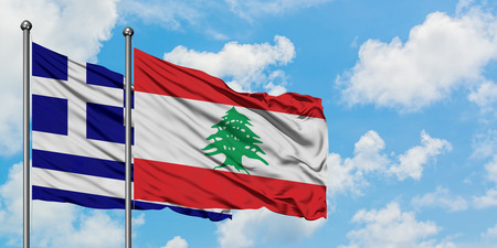 Greece and Lebanon flag waving in the wind against white cloudy blue sky together. Diplomacy concept, international relations.