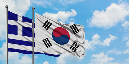 Greece and South Korea flag waving in the wind against white cloudy blue sky together. Diplomacy concept, international relations.