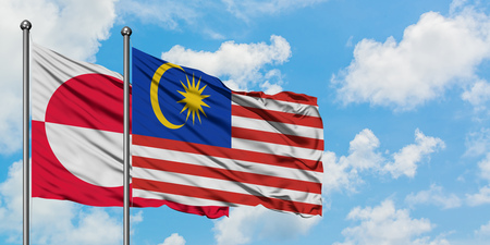Greenland and Malaysia flag waving in the wind against white cloudy blue sky together. Diplomacy concept, international relations.