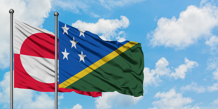 Greenland and Solomon Islands flag waving in the wind against white cloudy blue sky together. Diplomacy concept, international relations.