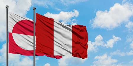 Greenland and Peru flag waving in the wind against white cloudy blue sky together. Diplomacy concept, international relations. Stock Photo