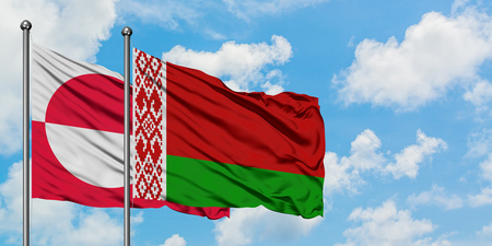 Greenland and Belarus flag waving in the wind against white cloudy blue sky together. Diplomacy concept, international relations.