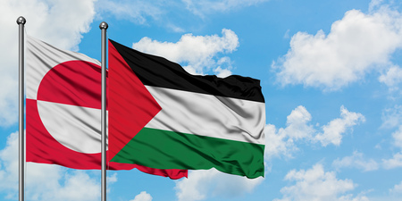 Greenland and Palestine flag waving in the wind against white cloudy blue sky together. Diplomacy concept, international relations.