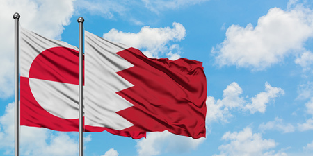 Greenland and Bahrain flag waving in the wind against white cloudy blue sky together. Diplomacy concept, international relations. Stock Photo