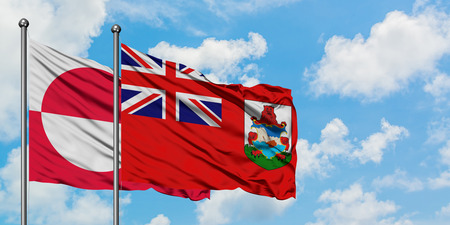 Greenland and Bermuda flag waving in the wind against white cloudy blue sky together. Diplomacy concept, international relations.