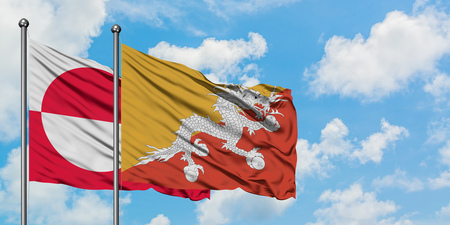 Greenland and Bhutan flag waving in the wind against white cloudy blue sky together. Diplomacy concept, international relations.