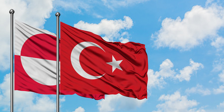 Greenland and Turkey flag waving in the wind against white cloudy blue sky together. Diplomacy concept, international relations.
