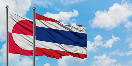 Greenland and Thailand flag waving in the wind against white cloudy blue sky together. Diplomacy concept, international relations.