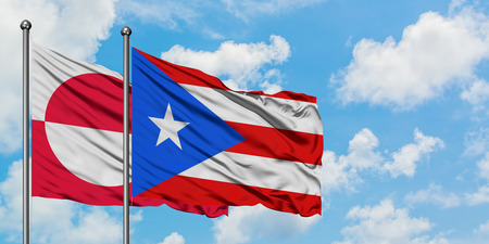 Greenland and Puerto Rico flag waving in the wind against white cloudy blue sky together. Diplomacy concept, international relations.