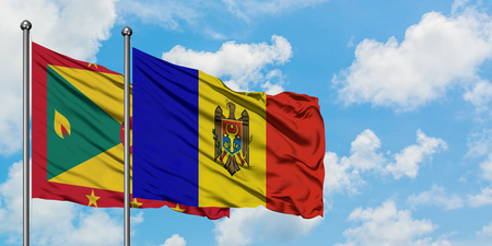 Grenada and Moldova flag waving in the wind against white cloudy blue sky together. Diplomacy concept, international relations. Stock Photo