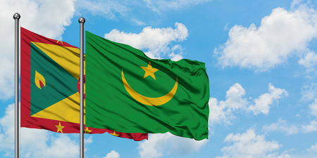 Grenada and Mauritania flag waving in the wind against white cloudy blue sky together. Diplomacy concept, international relations.
