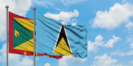 Grenada and Saint Lucia flag waving in the wind against white cloudy blue sky together. Diplomacy concept, international relations.