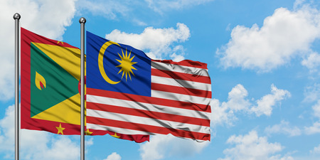 Grenada and Malaysia flag waving in the wind against white cloudy blue sky together. Diplomacy concept, international relations.