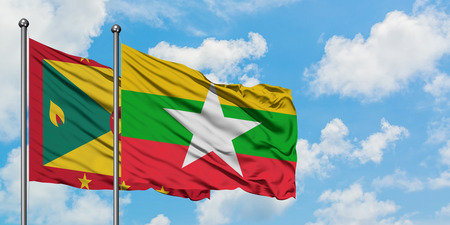 Grenada and Myanmar flag waving in the wind against white cloudy blue sky together. Diplomacy concept, international relations.