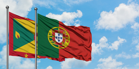 Grenada and Portugal flag waving in the wind against white cloudy blue sky together. Diplomacy concept, international relations. Stock Photo