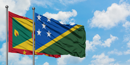 Grenada and Solomon Islands flag waving in the wind against white cloudy blue sky together. Diplomacy concept, international relations.