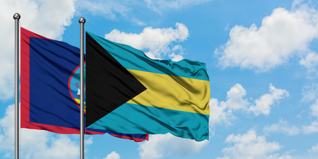 Guam and Bahamas flag waving in the wind against white cloudy blue sky together. Diplomacy concept, international relations. Stock Photo - 123579562