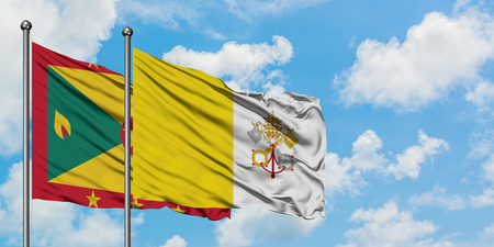 Grenada and Vatican City flag waving in the wind against white cloudy blue sky together. Diplomacy concept, international relations.