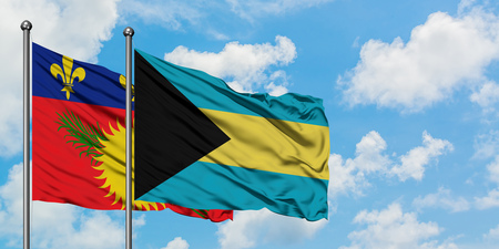 Guadeloupe and Bahamas flag waving in the wind against white cloudy blue sky together. Diplomacy concept, international relations. Stock Photo - 123579868
