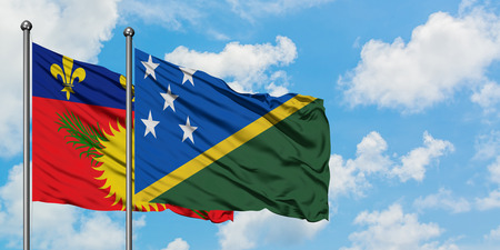 Guadeloupe and Solomon Islands flag waving in the wind against white cloudy blue sky together. Diplomacy concept, international relations. Stok Fotoğraf