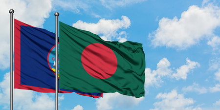 Guam and Bangladesh flag waving in the wind against white cloudy blue sky together. Diplomacy concept, international relations.