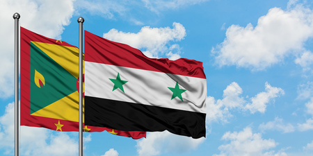 Grenada and Syria flag waving in the wind against white cloudy blue sky together. Diplomacy concept, international relations. Stockfoto
