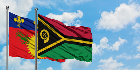 Guadeloupe and Vanuatu flag waving in the wind against white cloudy blue sky together. Diplomacy concept, international relations. Stock fotó