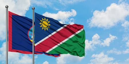 Guam and Namibia flag waving in the wind against white cloudy blue sky together. Diplomacy concept, international relations.