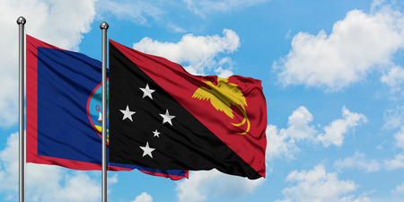 Guam and Papua New Guinea flag waving in the wind against white cloudy blue sky together. Diplomacy concept, international relations.
