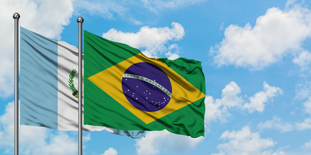 Guatemala and Brazil flag waving in the wind against white cloudy blue sky together. Diplomacy concept, international relations.