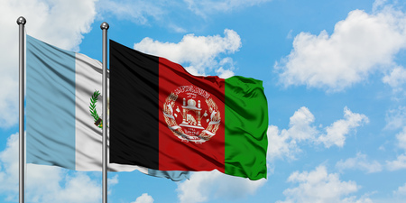 Guatemala and Afghanistan flag waving in the wind against white cloudy blue sky together. Diplomacy concept, international relations.
