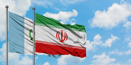 Guatemala and Iran flag waving in the wind against white cloudy blue sky together. Diplomacy concept, international relations.