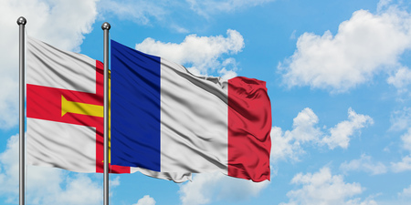 Guernsey and France flag waving in the wind against white cloudy blue sky together. Diplomacy concept, international relations. Stockfoto