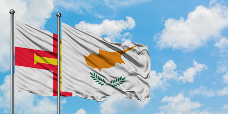 Guernsey and Cyprus flag waving in the wind against white cloudy blue sky together. Diplomacy concept, international relations. Standard-Bild