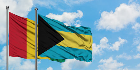 Guinea and Bahamas flag waving in the wind against white cloudy blue sky together. Diplomacy concept, international relations. Stock Photo - 123643314