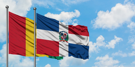 Guinea and Dominican Republic flag waving in the wind against white cloudy blue sky together. Diplomacy concept, international relations.